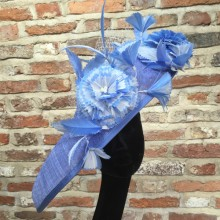 cornflower blue tilted sinamay disc with two tone ivory and pale blue  feather flowers, veiling and pearl detail.