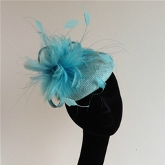 turquoise straw beret with feather trimming.