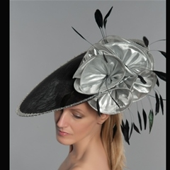 dramatic black tilted disc with silver flower and coque feather detail. set on a headband.