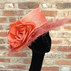 Unusual orange medium brim hat with feather brim and rose detail.