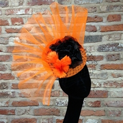 Bold orange fascinator with black rose and veiling detail.